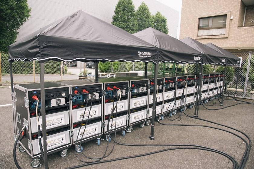 ソーラーパネルと繋ぐことですぐに蓄電、そのままステージ裏で発電できるコンパクトなシステム。常時13台が蓄電スタンバイ